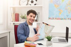 Young man reading map, planning vacation. Young happy man reading map and having coffee at home. Handsome guy preparing for vacation, planning route of trip Stock Photo