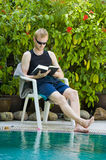 Young man reading nearby the swimming pool Royalty Free Stock Photos