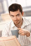 Young man reading news drinking tea at home Royalty Free Stock Photos
