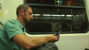 Young man reading news online, using app, texting on smartphone in metro train. Stock footage stock footage