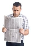 Young man reading newspaper Stock Images