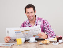 Young Man Reading Newspaper At Breakfast Royalty Free Stock Image
