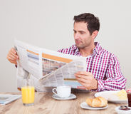 Young Man Reading Newspaper At Breakfast Stock Photography