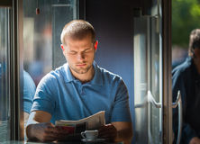 Young man reading a newspaper Stock Photos
