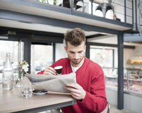 Young man reading newspaper while drinking coffee in cafe Stock Photography