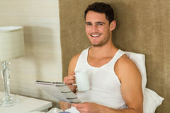 Young man reading newspaper while holding a cup of tea Royalty Free Stock Images