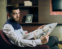 Young man reading newspaper Royalty Free Stock Images