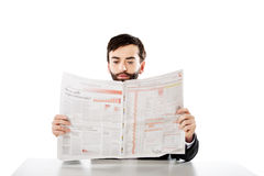 Young man reading newspaper in the office. Stock Images