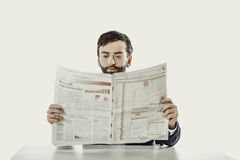 Young man reading newspaper in the office. royalty free stock photos