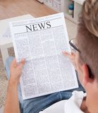 Young man reading newspaper Royalty Free Stock Photos