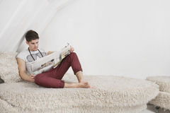 Young man reading newspaper while sitting on fur sofa Royalty Free Stock Image