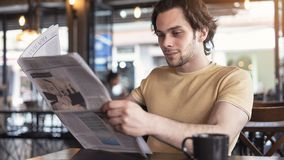 Young man reading the newspaper royalty free stock photography