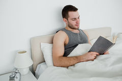 Young man reading a novel. In his bedroom Stock Photo