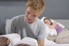 Young Man Reading Novel In Bedroom Royalty Free Stock Photo