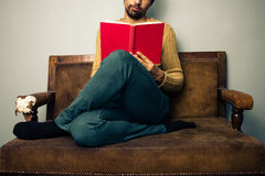 Young man reading on old sofa Stock Image