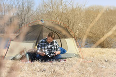 Young Man Reading Ourside Tent Royalty Free Stock Image