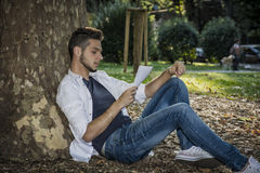 Young Man Reading Paper Sheets Relaxing at Park Royalty Free Stock Image