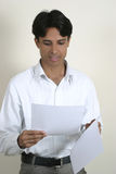 Young man reading papers. Young indian reading important papers Stock Photos