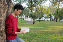 Young man reading in the park Royalty Free Stock Photos