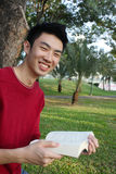 Young man reading in the park Stock Image