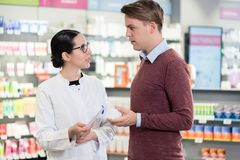 Young man reading the prescription of an important medicine next to a pharmacist Stock Photography