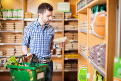 Young man reading a product label. Attractive man with a beard reading a product label while buying groceries at a store Royalty Free Stock Image