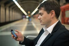 Young man reading sms on smartphone in underground. Young businessman with smartphone reading a text message in subway. Blurred underground station in background royalty free stock images