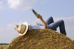 Young man reading on a straw bale Stock Photos