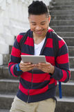 Young man reading a tablet. A handsome young man reading a tablet computer outdoors Stock Photography