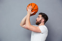 Young man reading to throw basket ball. Portrait of a young man reading to throw basket ball over gray background royalty free stock photo