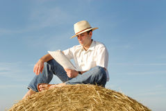 Young man reading on top of a straw bale Royalty Free Stock Photography