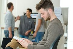 Young man reading in waiting area stock images