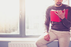 Young man reading by the window Royalty Free Stock Image
