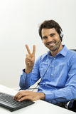 Young man reading written agreements for work. Attractive unshaven young man wearing a headset offering online chat and support on a client services of help desk Stock Photo
