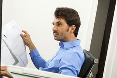 Young man reading written agreements for work Stock Photography