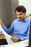 Young man reading written agreements for work. Young handsome man sitting at his desk in the office while reading written agreements and studying important Royalty Free Stock Images
