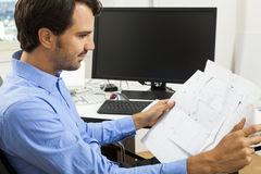 Young man reading written agreements for work. Young handsome man sitting at his desk in the office while reading written agreements and studying important Royalty Free Stock Photo