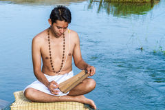 Young man reads ancient scripture. Stock Image
