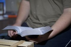 A young man reads the Bible, laying it on a wooden plank of boards. Stock Image