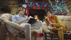 Young man reads a book while his mother surfing the Internet on mobile phone in Christmas night. Sitting by decorated Xmas tree stock footage
