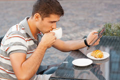 A young man reads the news on the device. Business breakfast Stock Photography
