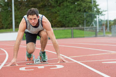 Young man ready to race on running track. Full length portrait of a young man ready to race on running track Royalty Free Stock Photo