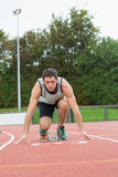 Young man ready to race on running track. Full length portrait of a young man ready to race on running track Stock Image