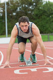 Young man ready to race on running track Royalty Free Stock Photos