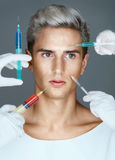 Young man ready to receive a botox injection while many hands holding syringes near his face. Stock Images