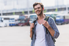 Young man is ready to travel. Happy male tourist is standing near bus station. He is carrying backpack and smiling Stock Image