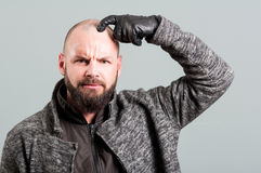 Young man with real beard scratching head and frown Royalty Free Stock Photos