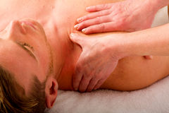 Young man receives massage to the shoulders Royalty Free Stock Photos