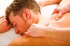 Young man receives massages to the shoulders. Young men receives massages to the shoulders by a woman Stock Photography