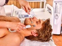 Young man receiving electric facial massage. Stock Photo
